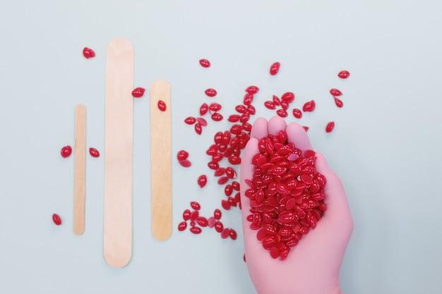 Рука в розовой перчатке держит гранулы красного воска для депиляции