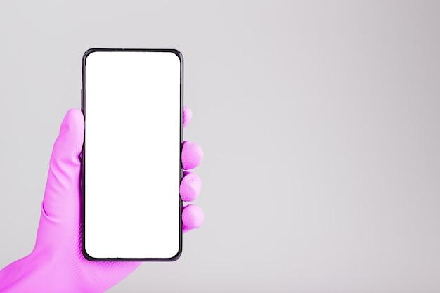 분홍색 의료 장갑에 손이 빈 흰색 화면이있는 검은 색 스마트 폰을 보유하고 회색 표면에 절연