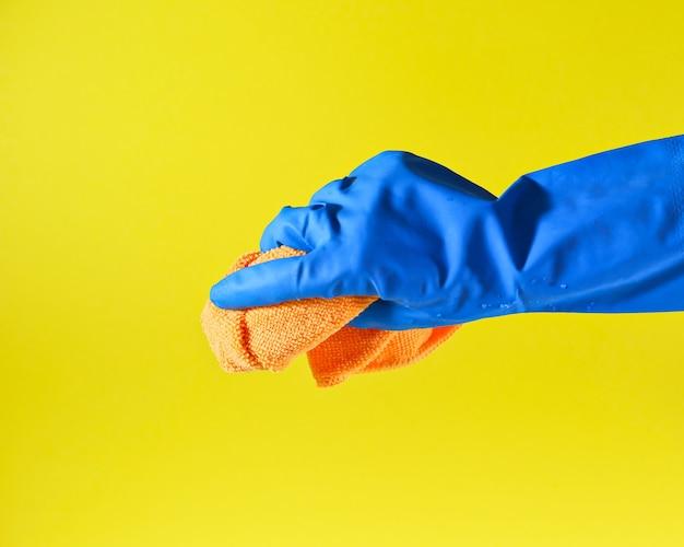 Рука в защитной перчатке держит тряпку