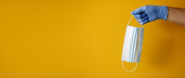 고무 장갑에 손을 노란색 배경에 보호 마스크를 보유하고 있습니다. 모든 종류의 미생물 및 바이러스에 대한 보호 개념