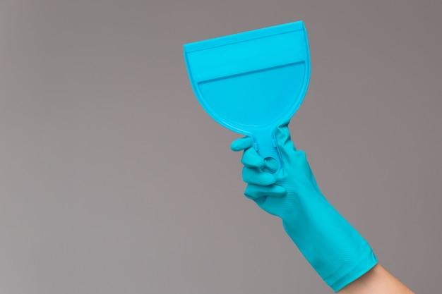 Рука в резиновой перчатке держит совок на нейтральном фоне.