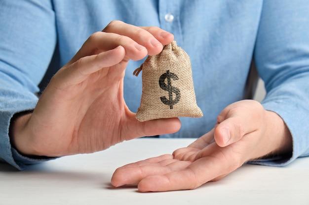 Рука в рубашке держит небольшую сумку с деньгами и знак доллара сша