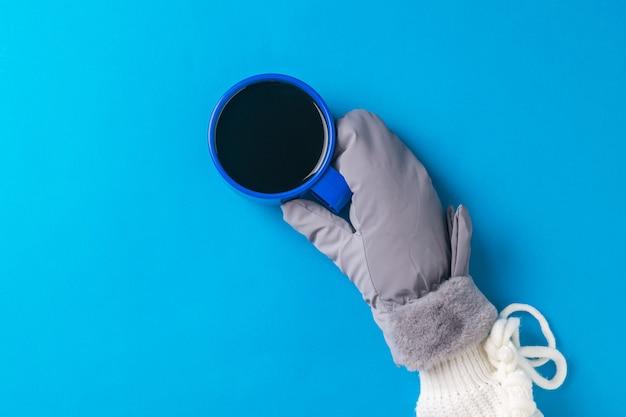 Рука в теплой перчатке с чашкой горячего кофе на синей поверхности. горячий напиток и варежки.
