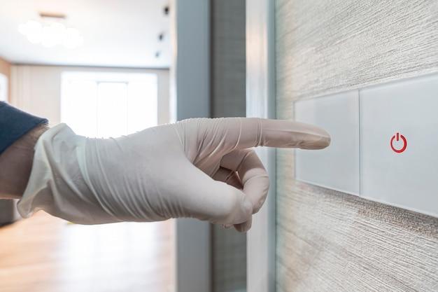 白い保護手袋をはめた手が電灯のスイッチを押します。公共の場所でのウイルスや細菌による感染のリスク。家庭衛生。