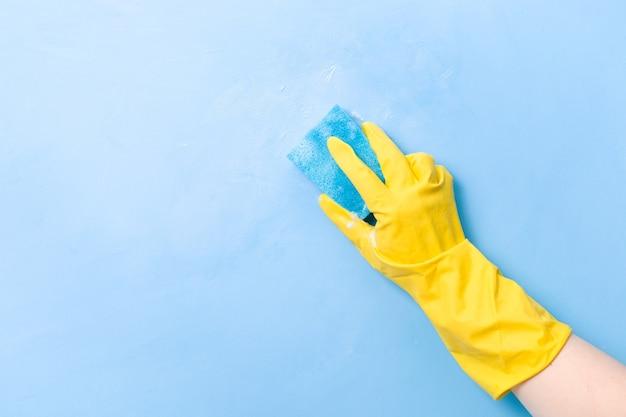 노란색 고무 장갑을 낀 손이 젖은 거품 푸른 스폰지로 벽을 닦습니다.