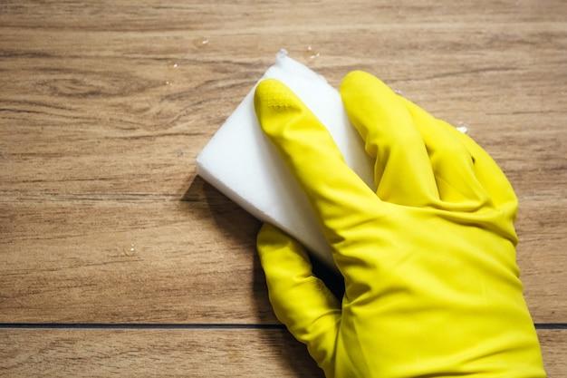 노란색 고무 장갑을 낀 손은 흰색 멜라민 스폰지로 나무 표면을 모방 한 젖은 타일을 닦습니다. 현대적인 욕실에서 청소. 선택적 초점