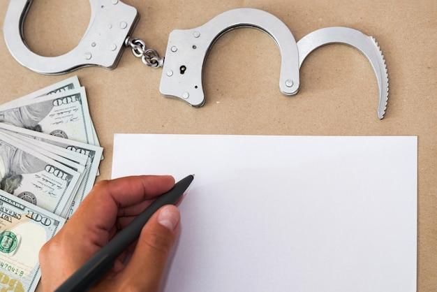 Рука в наручниках сидит за столом перед чистым листом бумаги и ручкой. концепция: задержанный пишет признание, заключенный подписывает документ.