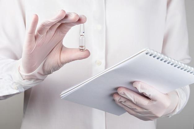 의료용 장갑을 낀 손에는 약이 든 앰플이 들어 있습니다.