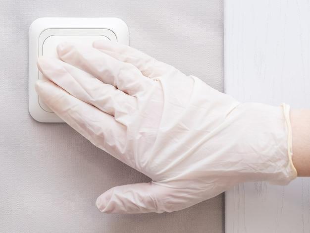 Рука в стерильных резиновых перчатках включает свет дома или в больнице.