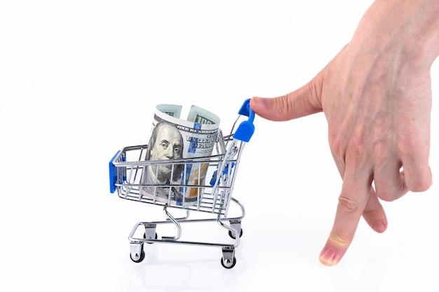 Рука в виде идущего человека скатывает тележку со стопкой стодолларовых купюр. скопируйте пространство.