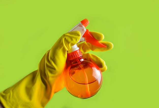 Рука в желтых резиновых перчатках держит красную бутылку с распылителем.