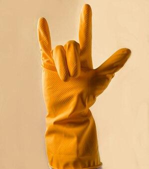黄色のゴム手袋をはめた手がロックホーンを示している