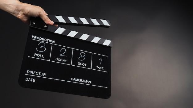 한 손이 비디오 제작, 영화, 영화, 영화 산업에서 검은색 클래퍼 보드나 영화 슬레이트를 검정색 배경에 들고 있습니다. 숫자로 작성되어 있습니다.