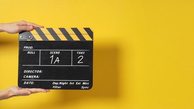 手は黄色の背景に黒いカチンコまたは映画のスレートを持っています。それは数字を書いています。