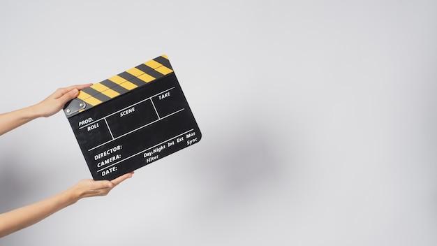 手は白い背景に黒と黄色のカチンコまたは映画のスレートを持っています。それは数字を書いています。