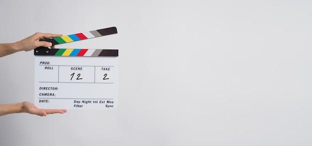 手は、黒い背景でビデオ制作や映画、映画、映画産業でのカチンコや映画のスレートの使用を保持しています。数で書いています。