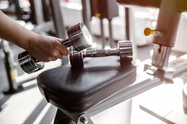 手がトレーニング装置からダンベルを拾っています。