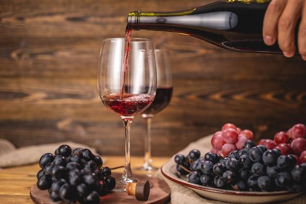 손은 나무 테이블에 포도 무리의 배경에 대해 병에서 유리에 마른 레드 와인을 붓고있다