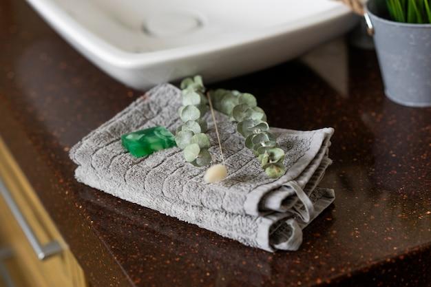 Мыло ручной работы и зеленая ветка эвкалипта лежат на сером хлопковом полотенце.