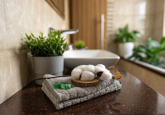 Мыло ручной работы и белый хлопок лежат на сером хлопковом полотенце в современной ванной комнате.