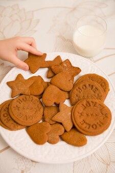 갓 만든 홈 홀리데이 쿠키를 시작 하트와 원 모양으로 가져가는 아이의 손