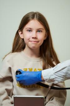Рука врача держит стетоскоп, слушая сердцебиение молодой пациентки. счастливая девушка с длинными волосами держит плюшевого мишку на приеме у врача.