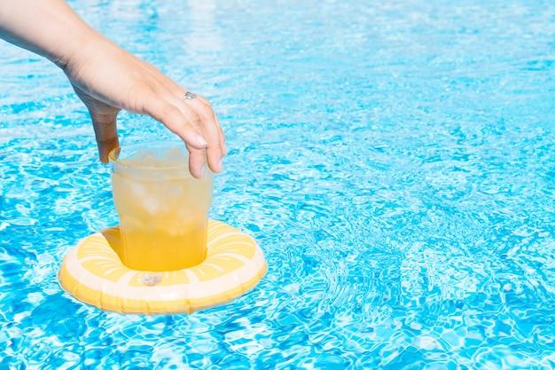 Рука женщины, держащей фруктовый сок в надувном лимоне у бассейна, летние каникулы