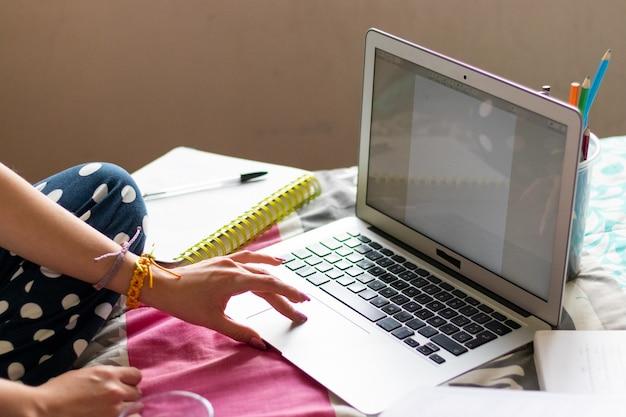 노트북에서 문서를 스크롤하는 젊은 여성의 손, 노트북은 컬러 펜과 메모장으로 둘러싸인 침대 위에 있습니다.