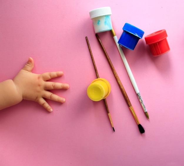 Рука ребенка, рисующего линии и формы разноцветными мелками.