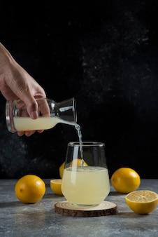 유리 컵에 레몬 주스를 붓는 손.