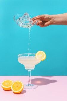 青とピンクの背景にレモンジュースをマルガリータカクテルに注ぐ手はメキシコを飲みます