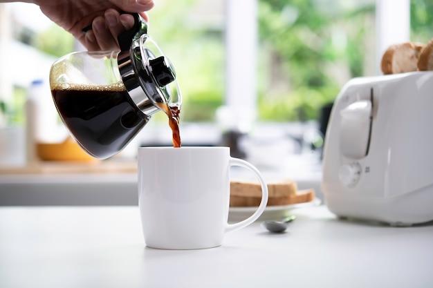 부엌에서 테이블에 컵에 김이 나는 커피를 붓는 손