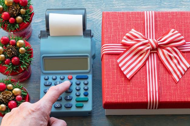 リボン付きの赤いギフトボックスとコーン付きの小さなクリスマスツリーの横にあるレジのボタンを押す手。ギフトの金額の計算。クリスマスプレゼントの購入