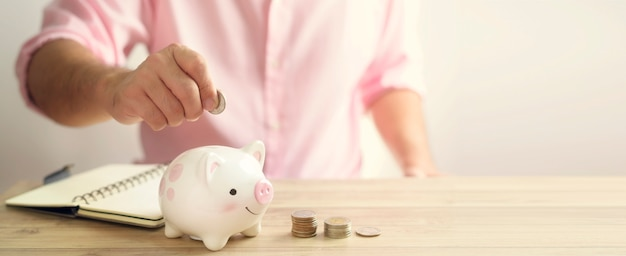 お金のコインを貯金箱に入れている手。将来の投資コンセプトのための節約お金。