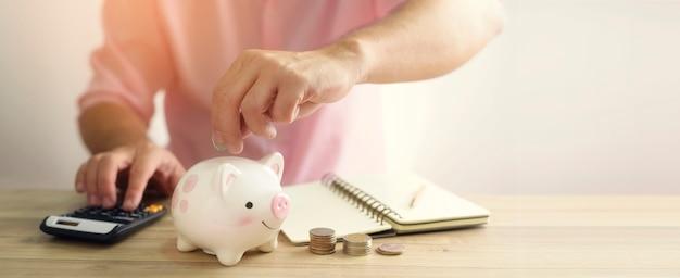 돼지 저금통에 돈을 동전을 넣어 손입니다. 미래 투자 개념을위한 저축 돈. 프리미엄 사진