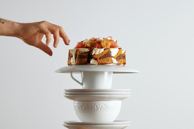Рука тянется за кусочком красивого светло-коричневого бисквитного торта с шоколадом, сливками и грейпфрутом.