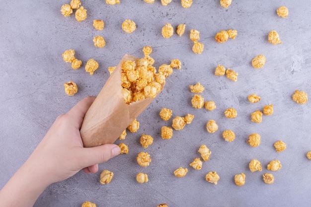 Рука проливает пачку попкорна в карамели на мраморном фоне. фото высокого качества