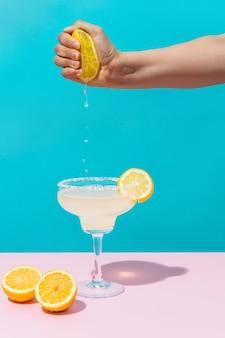 青とピンクの背景にレモンをマルガリータカクテルに絞る手メキシコを飲む