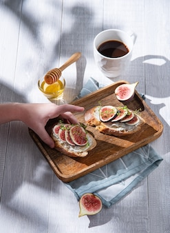 晴れた朝、手が木の板からイチジク、チーズ、蜂蜜のサンドイッチを取ります