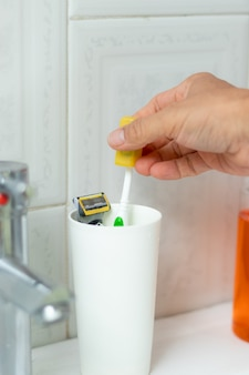 ガラスから歯ブラシを取る手