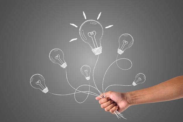 白いチョークで描かれた多くのアイデアを保持する手は、概念を描きます。