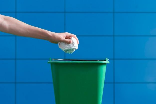 しわくちゃの紙片をゴミ箱に手で投げる
