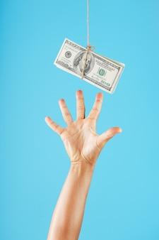 Рука пытается схватить пачку денег на веревке на синем.