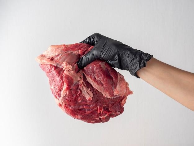 黒い手袋をした手は、明るい背景に新鮮な生の霜降り肉を持っています