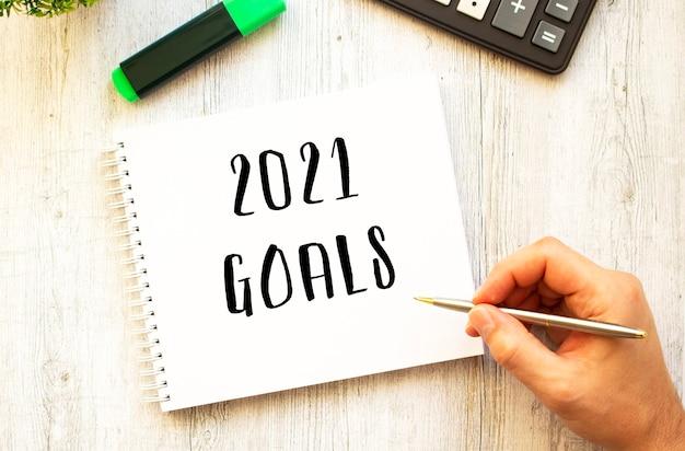Рука с ручкой пишет текст цели 2021 в блокноте на деревянном столе
