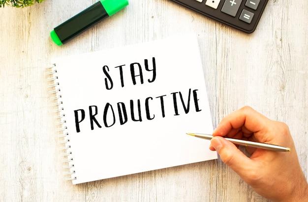 펜으로 손이 나무 책상 위의 노트북에 '생산성 유지'라는 텍스트를 씁니다.