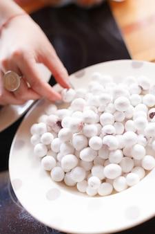 Рука с кольцом берет маленькие белые конфеты с белой тарелки
