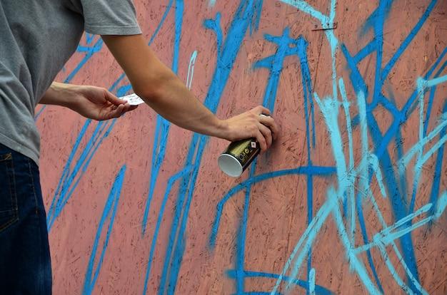 스프레이 캔이있는 손은 벽에 새로운 낙서를 그립니다.