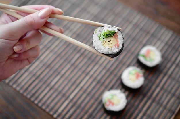Рука с палочками для еды держит суши-ролл на фоне сервировочного коврика из бамбуковой соломы. традиционная азиатская кухня.