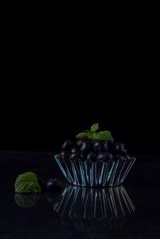 검정색 배경에 있는 금속 그릇에 블루베리 한 줌.